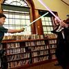 "ALLEGRA BOVERMAN/Staff photo. Gloucester Daily Times. Manchester: Jack Morgan, 9, left, duels with Jedi Master Jim at Manchester Public Library on Monday during a ""Jedi Knights in Training"" workshop. Participants took part in various challenges, including a ""Jedi Force Magic Show,"" where they ""used the force"" to change a balloon into a giant star flower. They also participated in a ""laser balloon barrage"" where Jedi Master Jim would fire long, skinny balloons at the children and they had to catch and fire them back at him."
