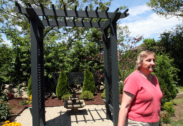 ALLEGRA BOVERMAN/Staff photo. Gloucester Daily Times.Rockport: Nan Blue of 14 Eden Road near the pergola and fountain in her garden on Thursday. Her gardens are on the Coastal Gardens tour on Friday and Satuday in Rockport.