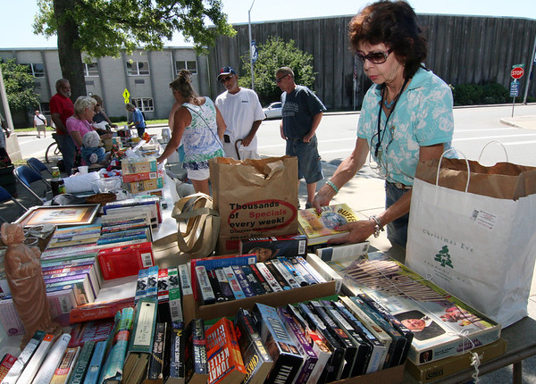 ALLEGRA BOVERMAN/Staff photo. Gloucester Daily Times. Gloucester: Robin French of Essex, right, who works with the social day care program at the Rose Baker Center in Gloucester, arranges more books at the Christmas in July fundraiser outside the center on Friday morning. There were raffles and bargains to help support the group.