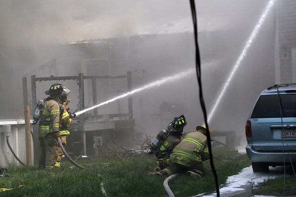 ALLEGRA BOVERMAN/Staff photo. Gloucester Daily Times. Gloucester: Firefighters work at the scene of a fire at 2 Ashland Place on Monday afternoon in Gloucester.