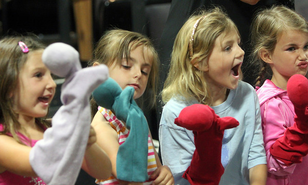 """Allegra Boverman/Staff photographer. Gloucester Daily Times. Gloucester: Roxie Myhrum, artistic director of the Puppet Showplace Theatre of Brookline, gave a puppeteering workshop at the Gloucester Stage Company's Youth Acting Workshops on Friday. She also coached the actors in the GSC's current production of """"Carnival."""" From left are: Annabella Iacono, Annaliese Frontiero,  Emily Hendrickson and her cousin Caroline Hanson, all 6 were having their puppets applaud for their fellow participants."""