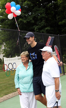 ALLEGRA BOVERMAN/Staff photo. Gloucester Daily Times. Rockport: Professional tennis player John Isner, center, poses for a photo with Janice and Peter Beacham of Rockport during a visit Isner made to a home in Rockport on Monday. Isner will be in the Olympics in London and was to leave for there Monday night after playing with the Boston Lobsters on Monday evening at Ferncroft Country Club against the Philadelphia Freedoms.