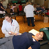 ALLEGRA BOVERMAN/Staff photo. Gloucester Daily Times. Gloucester: <br /> Christine Hammond, bottom, the grandmother of Caleigh Harrison, gives blood during a Red Cross blood drive in honor of Caleigh, who was to turn three on Friday. At upper right, also giving blood, was Caleigh's uncle, Brad Pyle, of Beverly. Collections specialists Sydney Fitzgerald, left, and Patrice Shaw, center back, assist them.