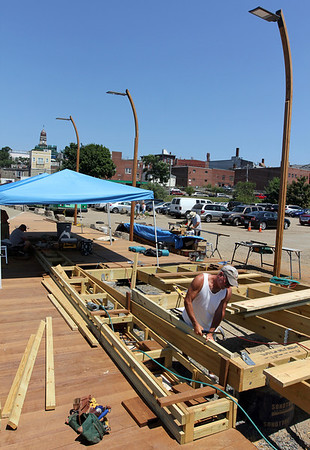 ALLEGRA BOVERMAN/Staff photo. Gloucester Daily Times. Gloucester: The Harborwalk area at the I-4, C-2 site is still under construction. A boardwalk with a built-in ramp is being built there. Dave Mason works at the site on Thursday.
