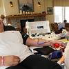 ALLEGRA BOVERMAN/Staff photo. Gloucester Daily Times. Gloucester: Victoria Rogers, left, of Rockport, donates blood at a Red Cross blood drive held on Thursday at Gloucester House's Compass Rose Room, in honor of Caleigh Harrison, who would have turned three on Friday. Rogers is a friend of the Hammond family, Caleigh's mother's family. Collections specialist Heather Lanigan, right, attends to her.