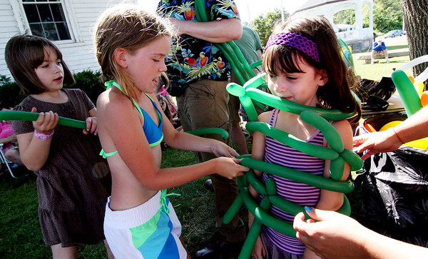 """ALLEGRA BOVERMAN/Staff photo. Gloucester Daily Times. Rockport: Sarah Patey, 6, of Rockport, far right, gets tied up during the """"vine wrap"""" game with balloons during Jungle Jim's Balloons, an event held by the Friends of the Rockport Library on Tuesday afternoon at the Legion Bandstand area on Beach Street. The program was part of the """"Dream Big - Read"""" summer reading program. Jungle Jim played balloon games  performed magic tricks and told stories. From left are Anna Drost, 6, and Jane Reilly, 8, both of Rockport."""