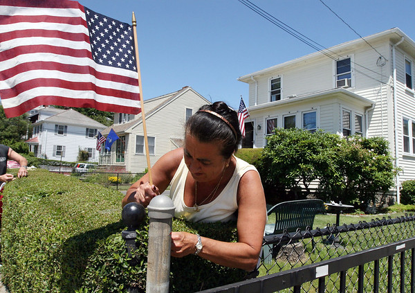 ALLEGRA BOVERMAN/Staff photo. Gloucester Daily Times. Gloucester: Sheila Brennan of Gloucester decorates her house on Centennial Avenue on Tuesday for the Fishtown Horribles Parade and July 4.