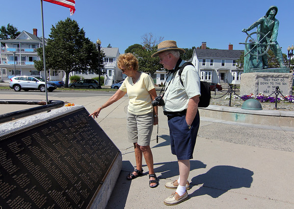 ALLEGRA BOVERMAN/Staff photo. Gloucester Daily Times. Gloucester: Millie Davis, left, originally of Hamilton, now of Spring Hill, Fla., and Rev. Robert Starrett, of Dover, Del., look at the newly reinstalled Cenotaph plaque listing the names of fishermen lost at sea, including ones from 2009 to 2011.