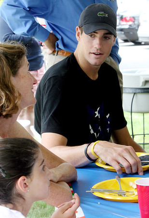 ALLEGRA BOVERMAN/Staff photo. Gloucester Daily Times. Rockport: Professional tennis player John Isner, right, chats with Anne Girian and her daughter Elizabeth Girian, 11, both of Manchester, during a visit Isner made to a home in Rockport on Monday. Isner will be in the Olympics in London and was to leave for there Monday night after playing with the Boston Lobsters on Monday evening at Ferncroft Country Club against the Philadelphia Freedoms.