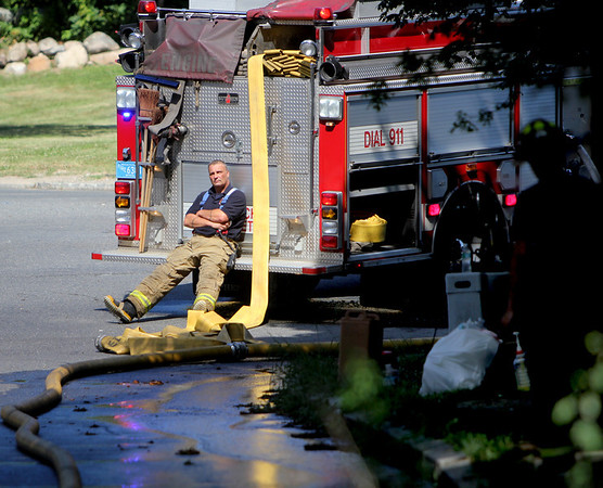 ALLEGRA BOVERMAN/Staff photo. Gloucester Daily Times. Gloucester: Firefighters who were working at the scene of a fire at 2 Ashland Place on Monday afternoon take a break.