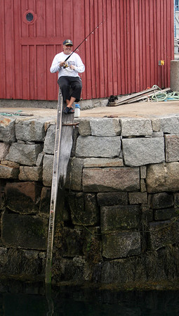 ALLEGRA BOVERMAN/Staff photo. Gloucester Daily Times. Rockport: Dan Tusinski of Rockport continues fishing after he caught a 31-inch striped bass he caught while fishing right at Motif No. 1 on Friday afternoon in Rockport. He will eat it tomorrow; he catches one every other week.