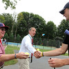 ALLEGRA BOVERMAN/Staff photo. Gloucester Daily Times. Rockport: Professional tennis player John Isner, right, signs tennis balls for Bill Irwin, center, of Essex, and Andy Kilgore, left, of Manchester during a visit Isner made to a home in Rockport on Monday. Isner will be in the Olympics in London and was to leave for there Monday night after playing with the Boston Lobsters on Monday evening at Ferncroft Country Club against the Philadelphia Freedoms.