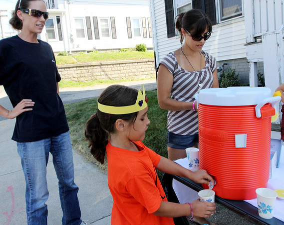 ALLEGRA BOVERMAN/Staff photo. Gloucester Daily Times. Gloucester: Bailee Militello, 6, of 29 East Main Street, center, was holding a lemonade stand at her house on Wednesday afternoon to benefit the Cardone family of 2 Ashland Place who had a big fire at their home on Monday. The lemonade sale will continue on Thursday from 2:30 - 4:30 p.m. Alicia Marchant, left, got some lemonade. Bailee's mom, Brieana Militello, is at far right.