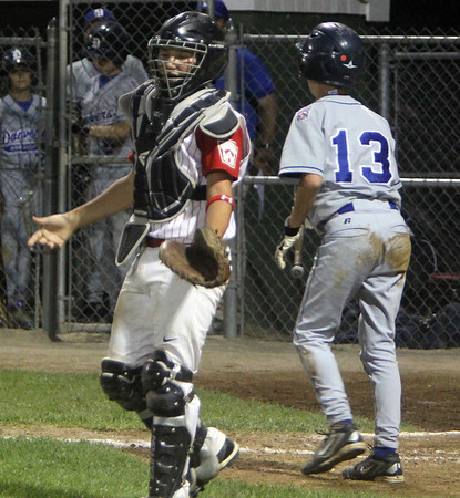 ALLEGRA BOVERMAN/Staff photo. Gloucester Daily Times. Beverly: Sal Costanzo, left, catcher for Gloucester American, protests the run of Danvers player Casey Bussone, right, during their game in Beverly on Friday evening.