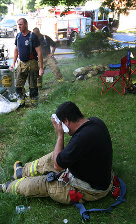 ALLEGRA BOVERMAN/Staff photo. Gloucester Daily Times. Gloucester: Firefighters who were working at the scene of a fire at 2 Ashland Place on Monday afternoon take a break in the shade and next to a fan that blew mist from a water tank.