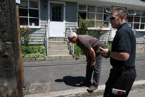 ALLEGRA BOVERMAN/Staff photo. Gloucester Daily Times. Gloucester: Gloucester Det. Steve Mizzoni, left, and a member of the Massachusetts State Police bomb squad examine the spot in front of Mame's Kitchen were a mailbox used to be installed. A pipe bomb destroyed it over the weekend and damaged a window in the eatery.