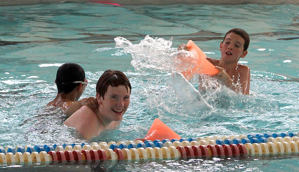 Jose Rodriguez, 13, and Gabe Leibensperger, 13, try to dodge a water attack from Cam Duquette, 12, while playing in the pool at the Glocuester YMCA. The Y recently opened the pool to the public, for free, as a way to beat the summer heat.