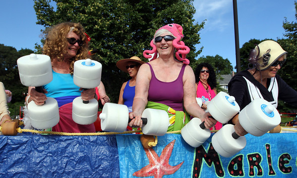 MARIA UMINSKI/GLOUCESTER DAILY TIMES From left to right, mermaids Jill Carter, Beverly Gillett and Jan Eell practice their barbell routine before the beginning of the Fishtown Horribles Parade on Thursday.