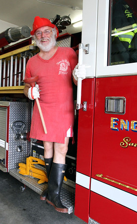 MARIA UMINSKI/GLOUCESTER DAILY TIMES George Ramsden hangs on the side of a Rockport firetruck decked out in his annual parade outfit. Ramsden is ending his 50 year run of leading the annual Rockport fireman band and fouth parade this weekend.