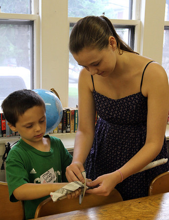 MARIA UMINSKI/GLOUCESTER DAILY TIMES Samantha Kane of Essex helps fit 7 year-old Stephen Ross of Essex, for his newspaper sword during the Pirate Festival at TOHP Burnham Library in Essex.