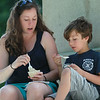 Six-year-old Milo Zeltzer, of Manchester, talks with his babysitter Melanie Baldini, of Ipswich, while eating ice cream on a statue in Masconomo Park on Wednesday afternoon. DAVID LE/Staff photo. 7/9/14.
