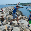 RYAN HUTTON/ Staff photo.<br /> From left, cousins Drew Fowler, 10, Jacob Fowler, 13, and Cole Fowler, 6, all of Beverly, leap among the rocks at Bearskin Neck in Rockport on Wednesday.