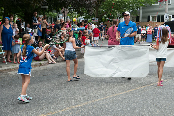 DESI SMITH/Staff photo.  Todd Carpenter of the Manchester Athletic Club (right) of Manchester play's tennis on the go with his daughter Tess 8, using the banner as the net, in the Manchester's 4th of July Parade on School Street Friday morning. <br />   July 4,2014
