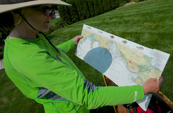 "RYAN HUTTON/ Staff photo.<br /> Deborah Walters shows just one of ""25 ponds worth"" of nautical charts that will guide her on her kayak trip from Maine to Guatemala to benefit the non-profit Safe Passage that helps children living in and around Guatemala City's garbage dump."
