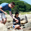 Ava Shaw, 8, and her father Patrick, visiting Eastern Point Lighthouse from New Jersey, look for sea glass on the beach on Wednesday afternoon. DAVID LE/Staff photo. 7/9/14.