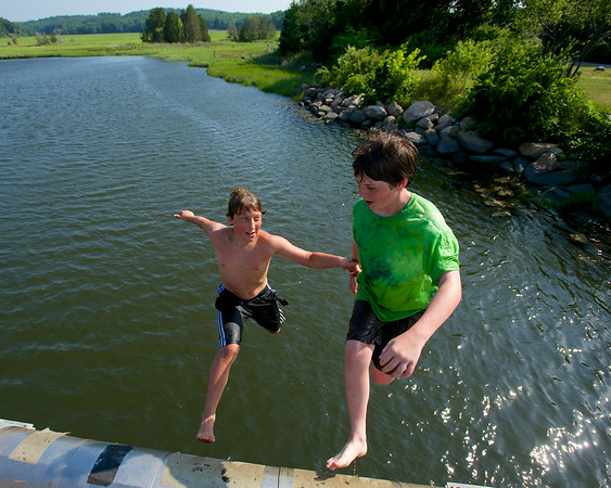 RYAN HUTTON/ Staff photo.<br /> Andrew Amigo, 10, of Essex, and Issac Notte, 12, of Gloucester, jump from the bridge on Main Street in Essex into the causeway to cool down on Wednesday.