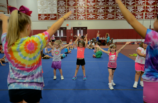 RYAN HUTTON/ Staff photo.<br /> Girls from the 5 to 7 age group practice some basic moves  at cheerleading camp in the Gloucester High School field house on Tuesday.