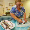 RYAN HUTTON/ Staff photo.<br /> Angela Snafilippo cleans hake fish to cook for Japanese journalist Akifumi Hoshina at the offices of the Gloucester Fishermen's Wives Association.