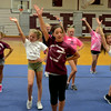 RYAN HUTTON/ Staff photo.<br /> Led by Eve Poliskey, 13, in front, the girls in the 11 to 13 age group finish off a cheer with some style at cheerleading camp in the Gloucester High School field house on Tuesday.
