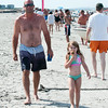 DESI SMITH/Staff photo.    Abby Horne 4, of Gloucester, enjoys a ice cream as she walks along with her dad Dean on Wingaersheek Beach Saturday afternoon in Gloucester.  July 12,2014