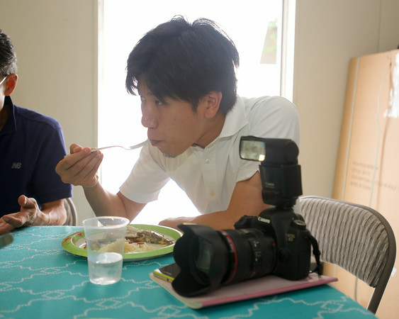 RYAN HUTTON/ Staff photo.<br /> Japanese journalist Akifumi Hoshina tries a mouthful of hake prepared by Angela Sanfilippo in the kitchen of the Gloucester Fishermen's Wives Association' offices.