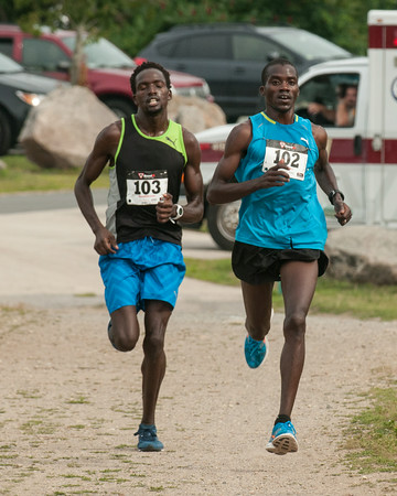 DESI SMITH/Staff photo.  Runners Amor Sang (left) and Glarius Rop, are side by side as they head for the finish line in the Seacoast 7k Saturday morning. Glarius Rop crossed first, that started and finished at Stage Fort Park.     July 19,2014