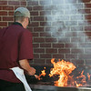 DESI SMITH/Staff photo.    Nikolas Kecyk from the 525 Tavern on Lexington Ave in Magnolia, has the grill all fired up, as he filps some burgers at the reopening and reception for the Magnolia fire station, Saturday morning.<br />   July 5,2014