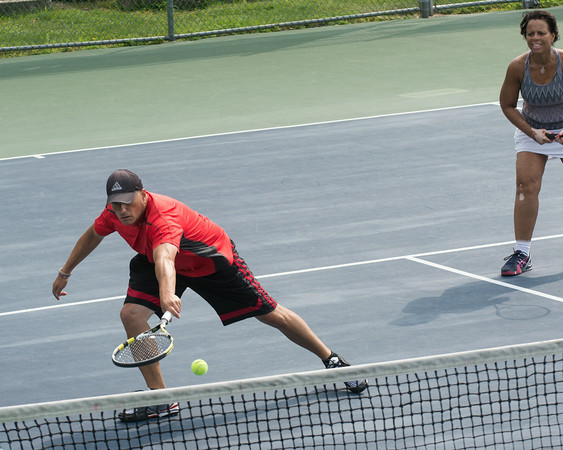 DESI SMITH/Staff photo. David Salah returns the ball in a doubles match with partner Gloria Lust-Phillips, against John Sperry and Nancy Gambal in the Bass Rocks Jerry Blitz Memorial Tennis Tournament held Saturday morning at Bass Rocks Tennis Courts.    July 26,2014
