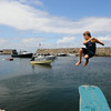 PAUL BILODEAU/Staff photo. Ewan McCarthy, 10 of Gloucester jumps of a diving board into Lanes Cove.