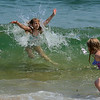 RYAN HUTTON/ Staff photo.<br /> Camille Maccarone, 7, of Manchester is hit by a wave while her friend Emily Haley, 7, of Manchester, right, turns to run from the water at Singing Beach in Manchester on Wednesday.