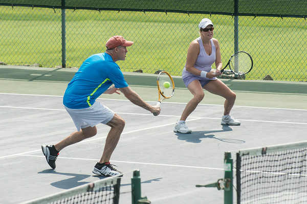 DESI SMITH/Staff photo. Scott MacIntosh returns the ball in a doubles match with partner Kathy Frick, against Will Daly and Tricia McInnis in the Bass Rocks Jerry Blitz Memorial Tennis Tournament held Saturday morning at Bass Rocks Tennis Courts.    July 26,2014