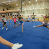 RYAN HUTTON/ Staff photo.<br /> The girls in the 8 to 10 age group practice some toe touch jumps at cheerleading camp in the Gloucester High School field house on Tuesday.