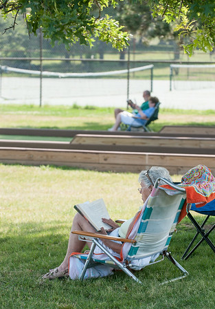 DESI SMITH/Staff photo.   Sandra Cloutman of Essex, and former Gloucester resident, returned to her favoite spot to relax and read her book Storm Cycle, on Stacy Boulavard Tuesday afternoon, as well as a couple in the background, who found some shade and a cool breeze.<br />   July 8,2014