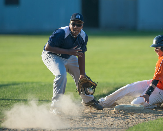DESI SMITH/Staff photo.    Manchester/Essex's 3rd basemen Peyton Cook plays the ball off the dirt, as Beverly's Hunter Flood slides safe into 3rd, Saturday afternoon at Cooney Field in Beverly.