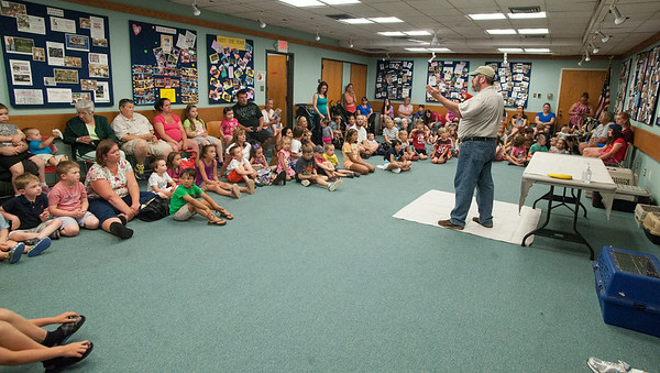 DESI SMITH/Staff photo.  Richard Roth of Creature Teachers, shows a large group of parents and childern a large macaw during during a live animal program at the Sawyer Free Library Monday afternoon.<br />   July 7,2014