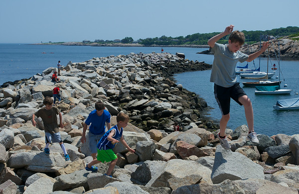 RYAN HUTTON/ Staff photo.<br /> From right, cousins Camden Thompson, 12, Cole Fowler, 6, Jacob Fowler, 13, and Drew Fowler, 10, all from Beverly, leap among the rocks at Bearskin Neck in Rockport on Wednesday.