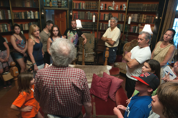DESI SMITH/Staff photo. John Pettibone, back to camera, stops a group in the library on a recent candlelight tour at Hammond Castle in Gloucester.