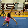 RYAN HUTTON/ Staff photo.<br /> Alli Smith, 11, works on her cartwheels as other girls practice stationary backflips at cheerleading camp in the Gloucester High School field house on Tuesday.