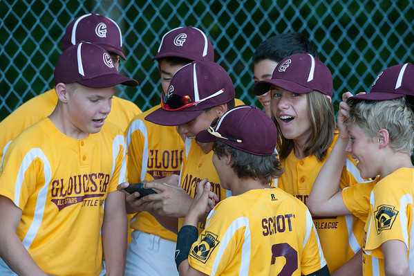 DESI SMITH/Staff photo.    Gloucester Little League players enjoy watching a video on a cell phone, while waiting for the Beverly vs Danvers game to end. They took on Hamilton/Wenham in the Williamsport Little League Playoffs Saturday evening at Harry Ball Field in Beverly. The team lost 7-4 after making a come back in the forth innning.<br />   July 5,2014