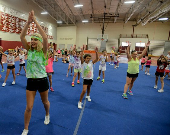 RYAN HUTTON/ Staff photo.<br /> Lexi Orlando, 16, left, leads the 8 - 10 age through some more complex cheers at cheerleading camp in the Gloucester High School field house on Tuesday.